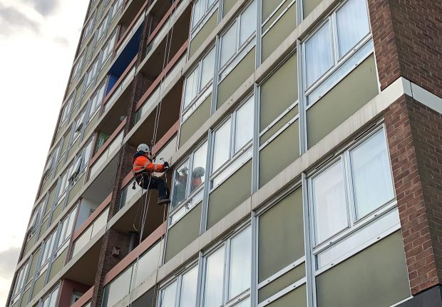 Man performing rope access cleaning